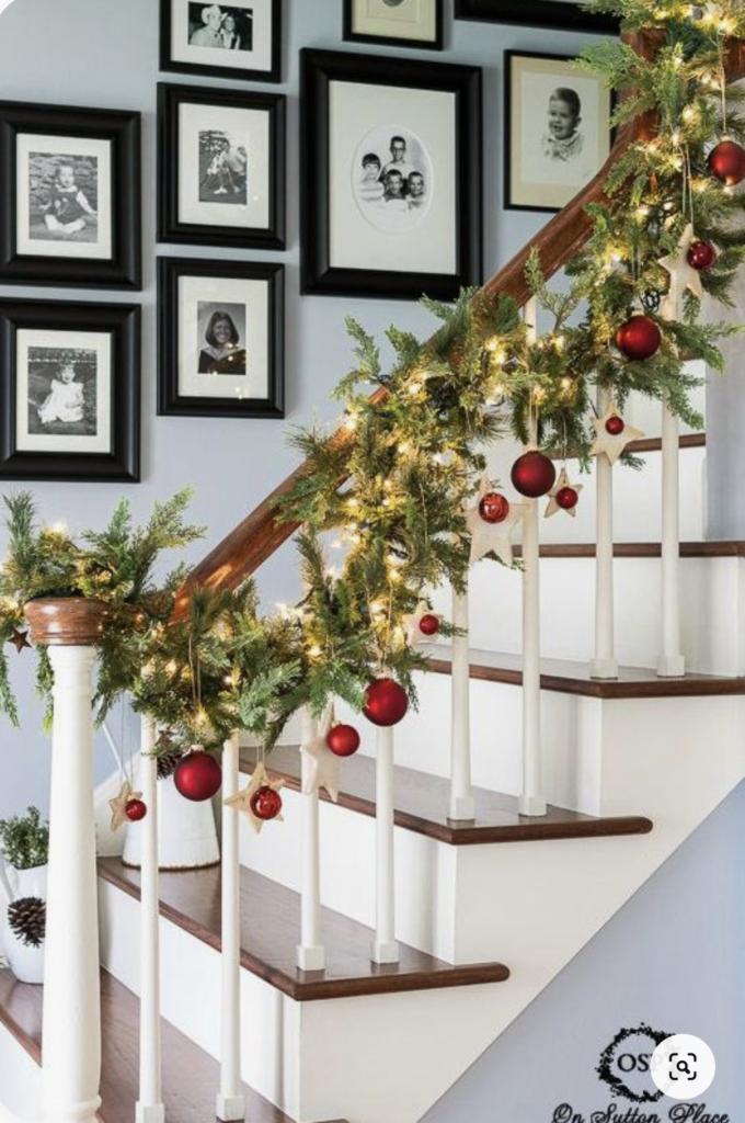 Scale da interni con decorazioni natalizie: palline rosse e ramo